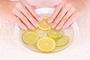 Руки в ванночке с кусочками лимона