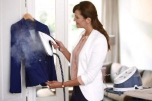 Женщина гладит куртку паром