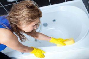 Женщина отбеливает ванну