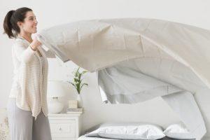 Женщина заправляет кровать