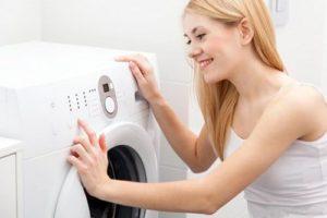Девушка запускает стиральную машину
