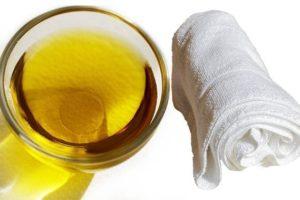 Растительное масло в стакане и белое полотенце