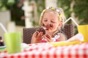 Измазанная шоколадным пирожным девочка