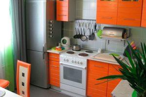 Холодильник и оранжевая кухня
