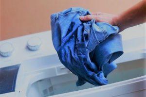 Постиранные джинсы вынимаются из стиральной машины