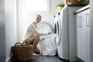 Девушка загружает белье в стиральную